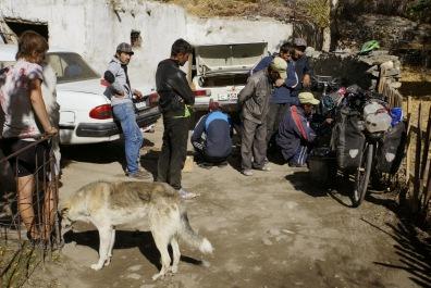 Locals in Tajikistan helping fix a broken pannier rack using wire coathangers